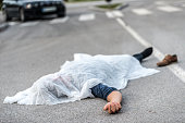 Covered body of a male person who was hit by a car