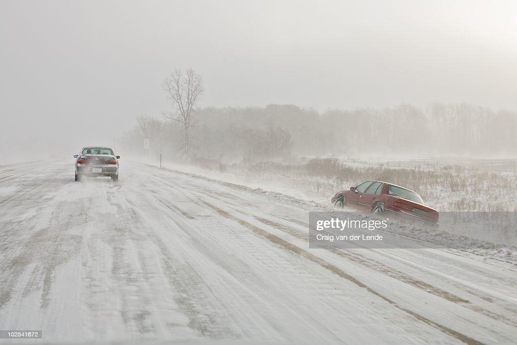 Car in ditch on snow covered highway : Stock Photo