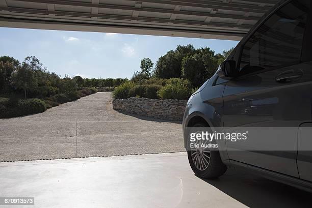 Car in garage leading toward driveway