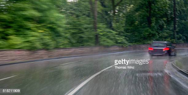 Car in heavy rain driving through a curve