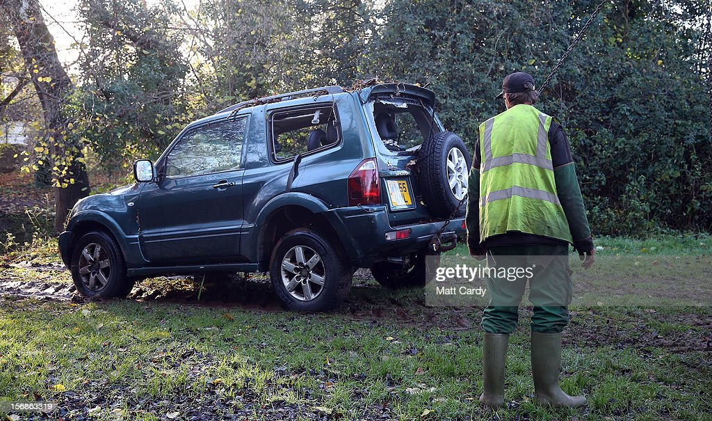 A car, in which a man died after being trapped in flood waters, is dragged by chains from under a bridge near to a ford at Rectory Fields, in Chew Stoke, on November 23, 2012 in Somerset, England. The man died after becoming trapped in his 4x4 car in flood water last night as heavy rain continued to bring chaos to large parts of the country.