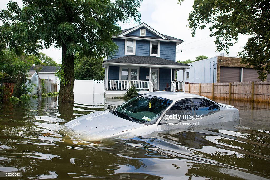 A car is abandoned on a flooded Reddington St. following heavy rains and flash flooding August 13, 2014 in Bayshore, New York. The south shore of Long Island along with the tri-state region saw record setting rain that caused roads to flood entrapping some motorists.