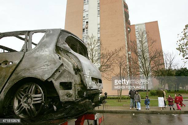 A car is being towed at the Maurice Thorez neighborhood as residents look on 04 November 2005 in Trappes Gang of youths torched more than 500 cars...