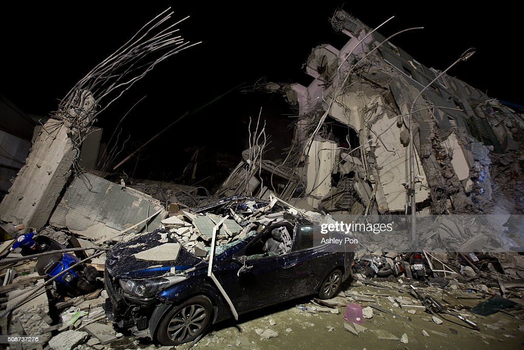 A car is damaged by the collapsed buildings on February 6, 2016 in Tainan, Taiwan. A magnitude 6.4 earthquake hit southern Taiwan early Saturday, toppling several buildings and killing at least five people in Tainan, according to local news reports.