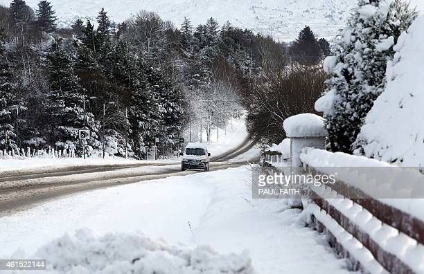 A car is driven along a road after heavy snow near Londonderry in Northern Ireland on January 14 2015 More than 100 schools and nurseries have been...