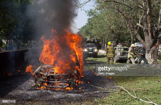 A car is engulfed in flames after a suicide car bomb exploded near the main gate of the NATO headquarters killing three Afghans and wounding 70 on...