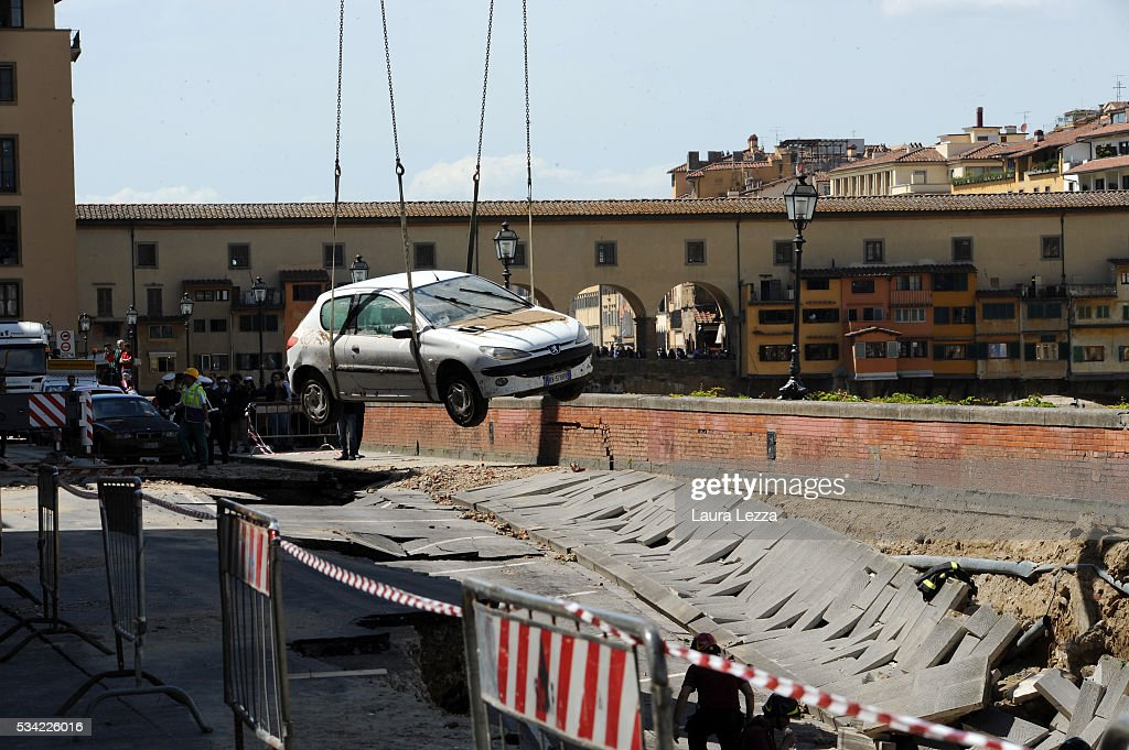 A car is lifted to safety after a road collapsed along the Arno river on May 25, 2016 in Florence, Italy. The deterioration of one or more water pipes opened a 200 m wide and 7m deep hole on Wednesday morning along the bank of the river Arno close to the famous Ponte Vecchio bridge. Many cars that were parked sunk and damages are thought to be around 5 millions euros.