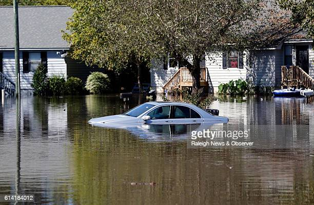 A car is nearly covered as the flood waters rise on Wednesday Oct 12 2016 at the Wyndham Circle duplex complex in Greenville NC