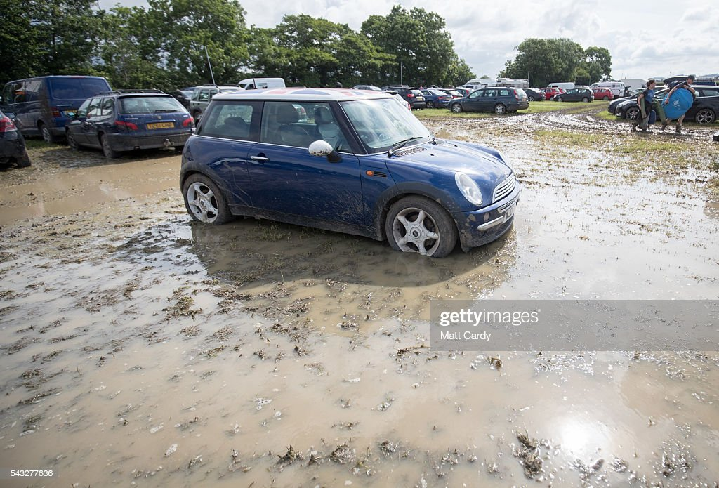 A car is parked in standing water as festival goers leave the Glastonbury Festival 2016 at Worthy Farm, Pilton on June 26, 2016 near Glastonbury, England. The Festival, which Michael Eavis started in 1970 when several hundred hippies paid just £1, now attracts more than 175,000 people.