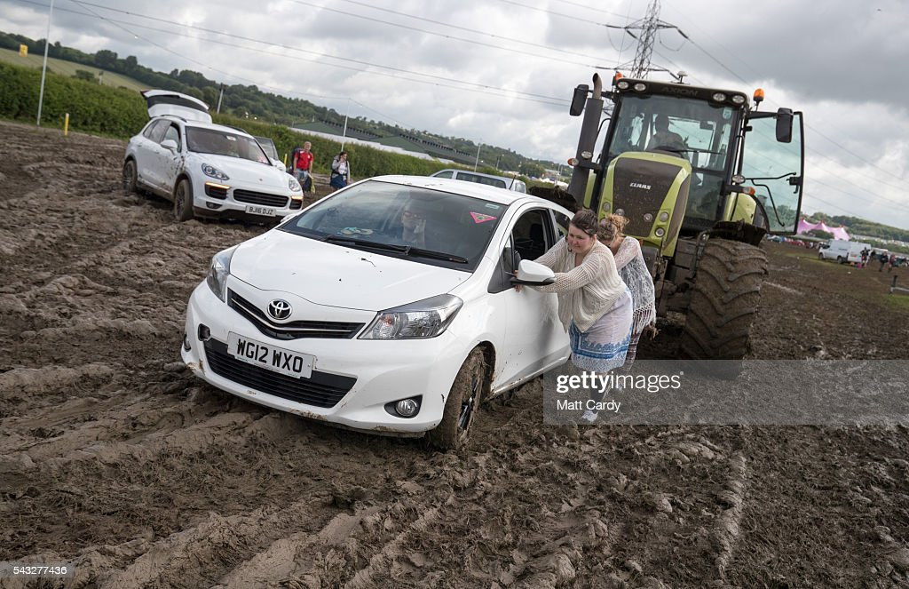 A car is pushed by a tractor as festival goers leave the Glastonbury Festival 2016 at Worthy Farm, Pilton on June 26, 2016 near Glastonbury, England. The Festival, which Michael Eavis started in 1970 when several hundred hippies paid just £1, now attracts more than 175,000 people.