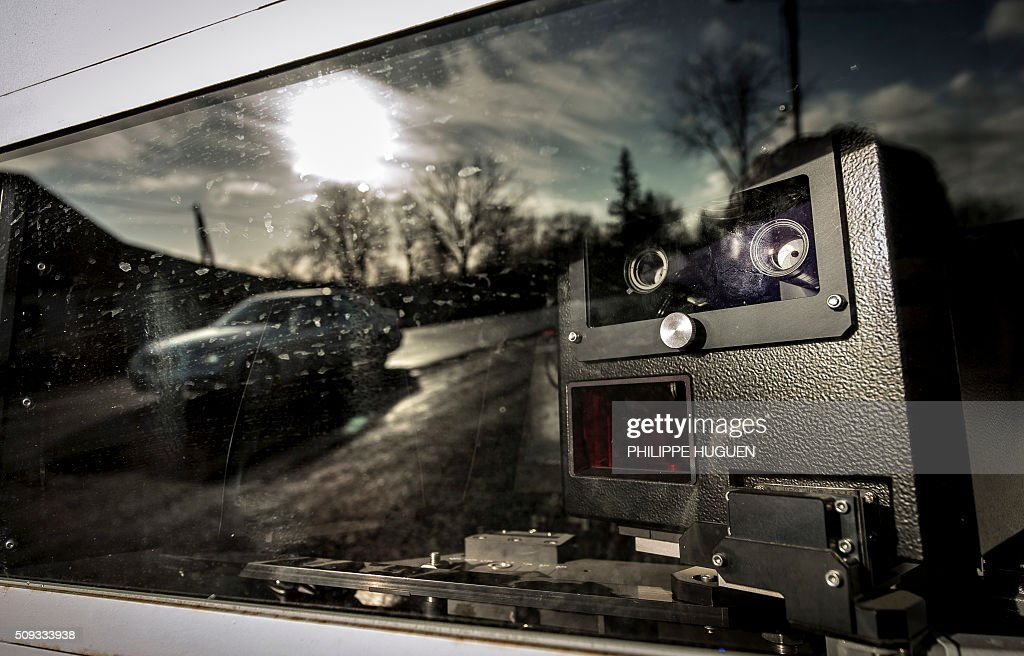 A car is reflected in a speed camera on the D939 in Aubigny-en-Artois on February 10, 2016, in the first area in France to be outfitted with 'luring signs'. Eleven signs reading 'For your safety, frequent use of speed cameras' will be installed on a portion of the by-road in the Pas-de-Calais department, but a speed camera will be hidden behind only one of the signs, which will be moved regularly. / AFP / PHILIPPE HUGUEN