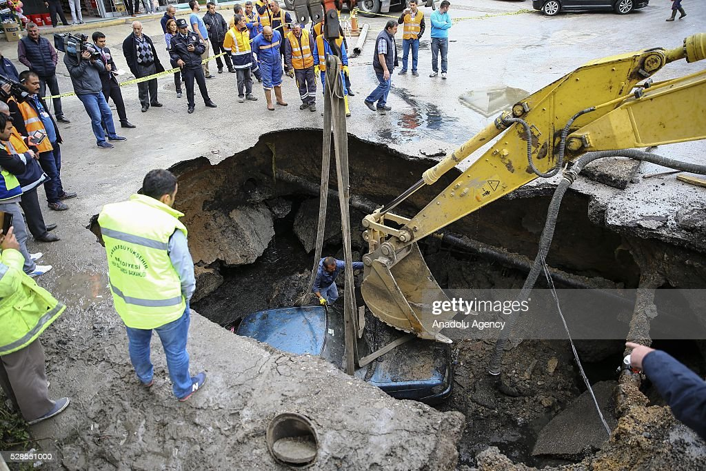 A car is removed by municipality team via a crane from the hollow, occurring after softened ground due to a bursted waterpipe in Ankara, Turkey on May 6, 2016.