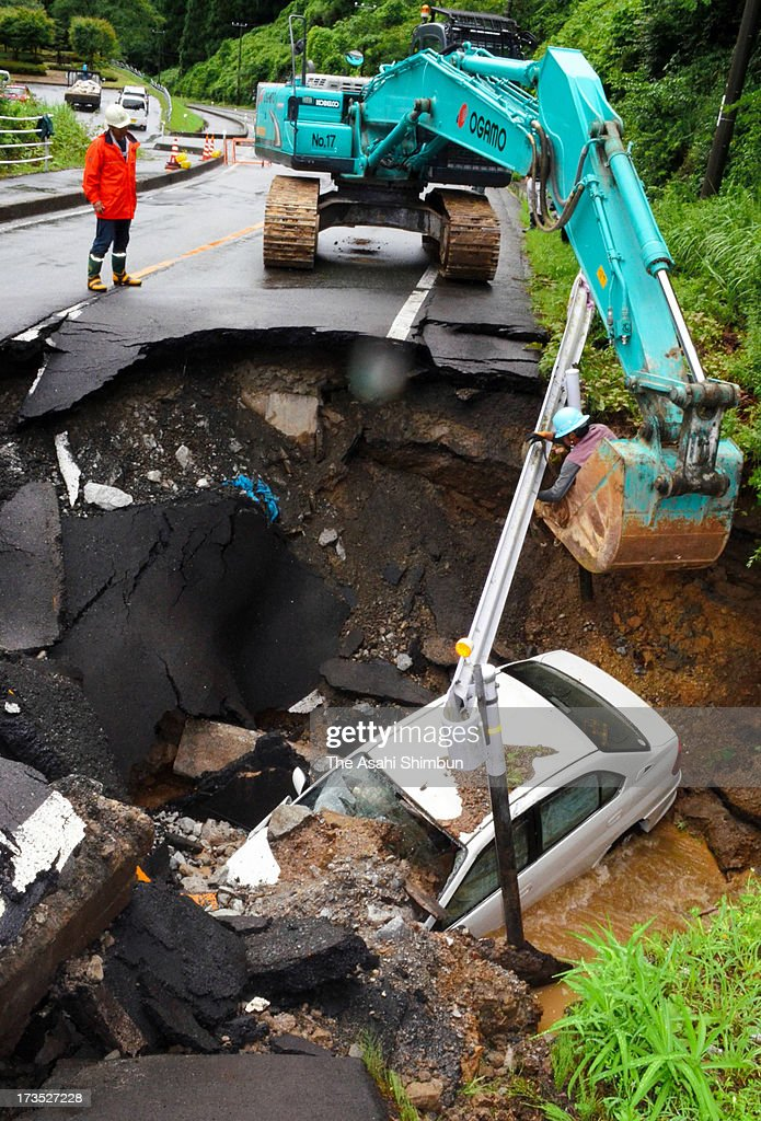 A car is salvaged from a collapsed road on July 15, 2013 in Misasa, Tottori, Japan. Three people were injured. Yonago city, Tottori prefecture's capital, recorded 66.5 millimeters of rain in an hour.