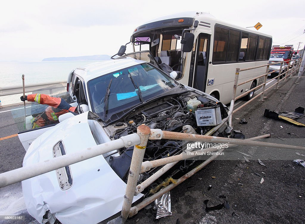 A car is seen crashed by a bus on January 5, 2014 in Fukuoka, Japan. As of January 6, 2014, one of men on the car has been killed and another has suffered a severe head injury and in coma.