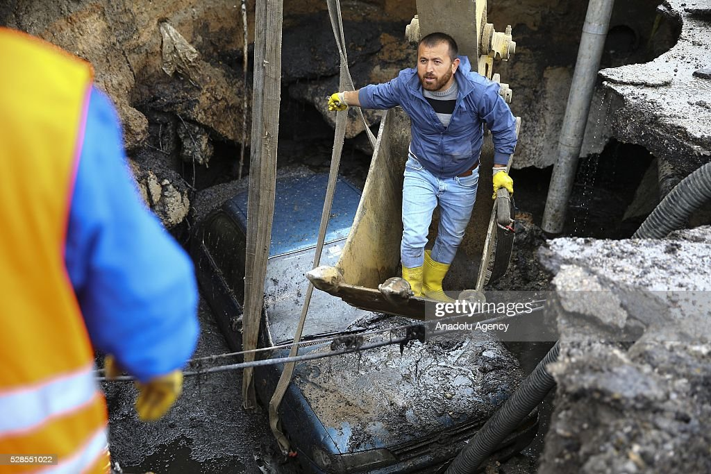 A car is seen in hollow, occurring after softened ground due to a bursted waterpipe in Ankara, Turkey on May 6, 2016. The car was removed via a crane by municipality team.