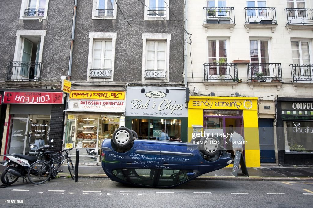 A car is seen parked on its roof, on July 8, 2014, in front upside down shop signs in a street of Nantes, western France, as part of the 'A journey to Nantes' (Le Voyage a Nantes) art festival. The event will run from June 27 to August 31, 2014. AFP PHOTO / JEAN-SEBASTIEN EVRARD ==RESTRICTED TO EDITORIAL USE, MANDATORY MENTION OF THE ARTIST UPON PUBLICATION, TO ILLUSTRATE THE EVENT AS SPECIFIED IN THE CAPTION==