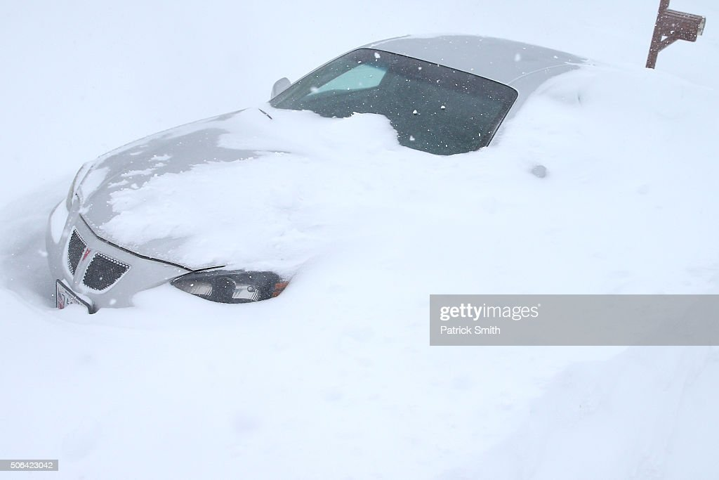 A car is seen under a shift drift on January 23 2016 in Forest Hill Maryland Heavy snow continued to fall in the the MidAtlantic region causing...