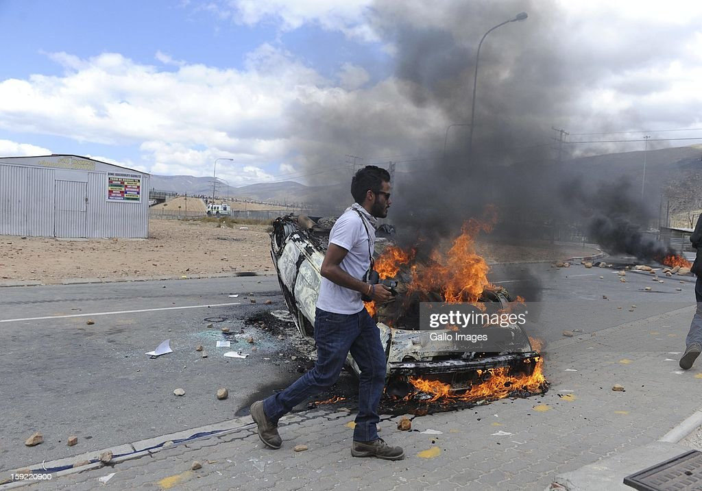A car is set on fire at the N1 highway De Doorns protest on January 9, 2013, in Cape Town, South Africa. The farm workers shut down the N1 by lighting tires on fire and placing large rocks on the road.