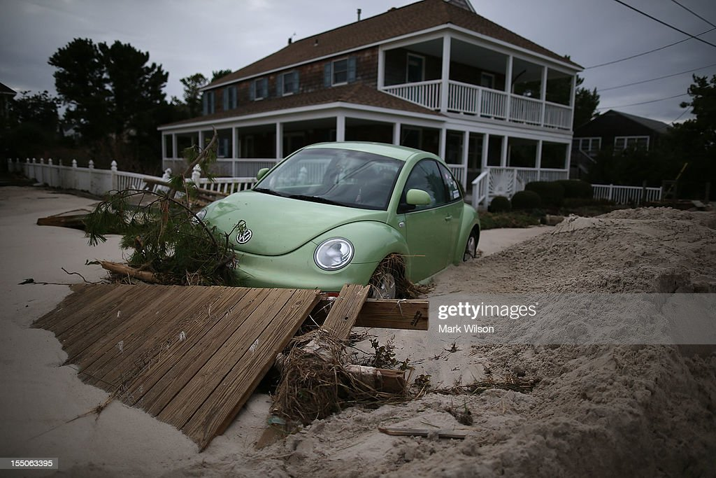 A car is submerged in sand and debris washed in from Hurricane Sandy, on October 31, 2012 in Long Beach Island, New Jersey. Earlier in the week Hurricane Sandy made landfall on New Jersey coastline bringing heavy winds and record floodwaters.