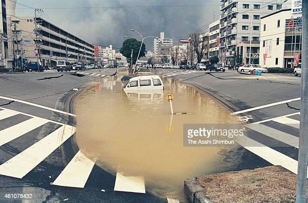 A car is sunk in a big puddle as the strong earthquake breaks waterpipe on January 17 1995 in Kobe Hyogo Japan Magnitude 73 strong earthquake jolted...