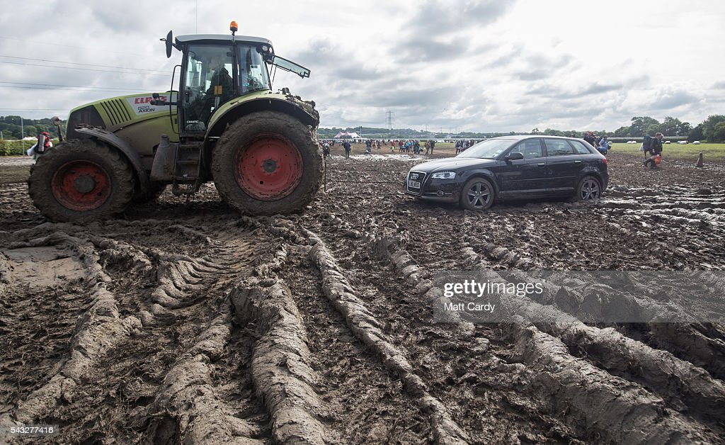 A car is towed by a tractor as festival goers leave the Glastonbury Festival 2016 at Worthy Farm, Pilton on June 26, 2016 near Glastonbury, England. The Festival, which Michael Eavis started in 1970 when several hundred hippies paid just £1, now attracts more than 175,000 people.