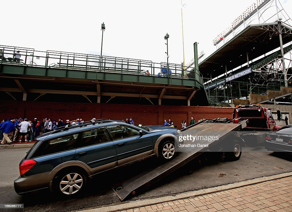 A car is towed from Waveland avenue outside of Wrigley Field before the Opening Day game between the Chicago Cubs and the Milwaukee Brewers at...