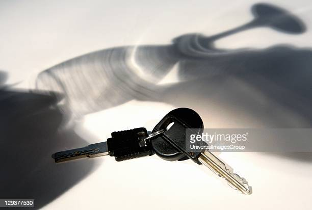 Car key with shadow of man drinking wine