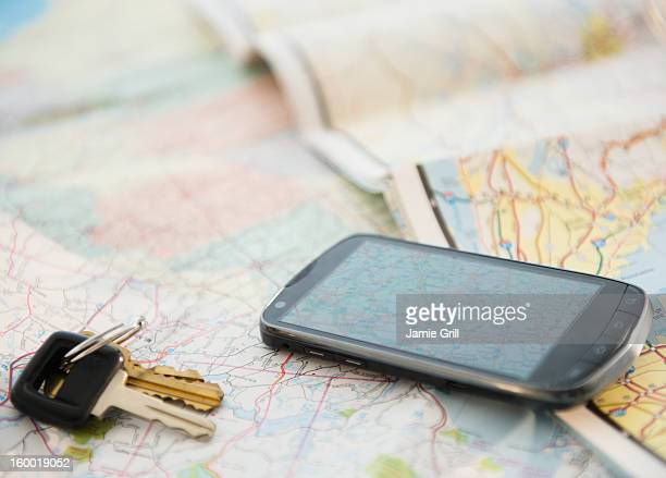 Car keys and smartphone on map