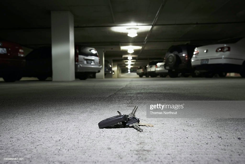 Car keys on concrete in parking garage (focus on car keys)