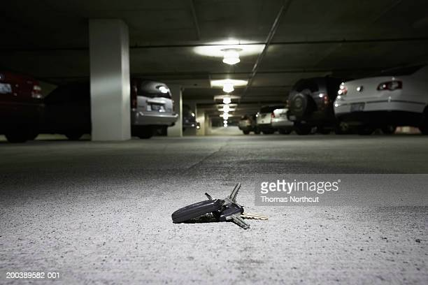 Car keys on concrete in parking garage (focus on car keys)