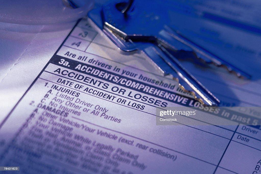Car keys on top of insurance form