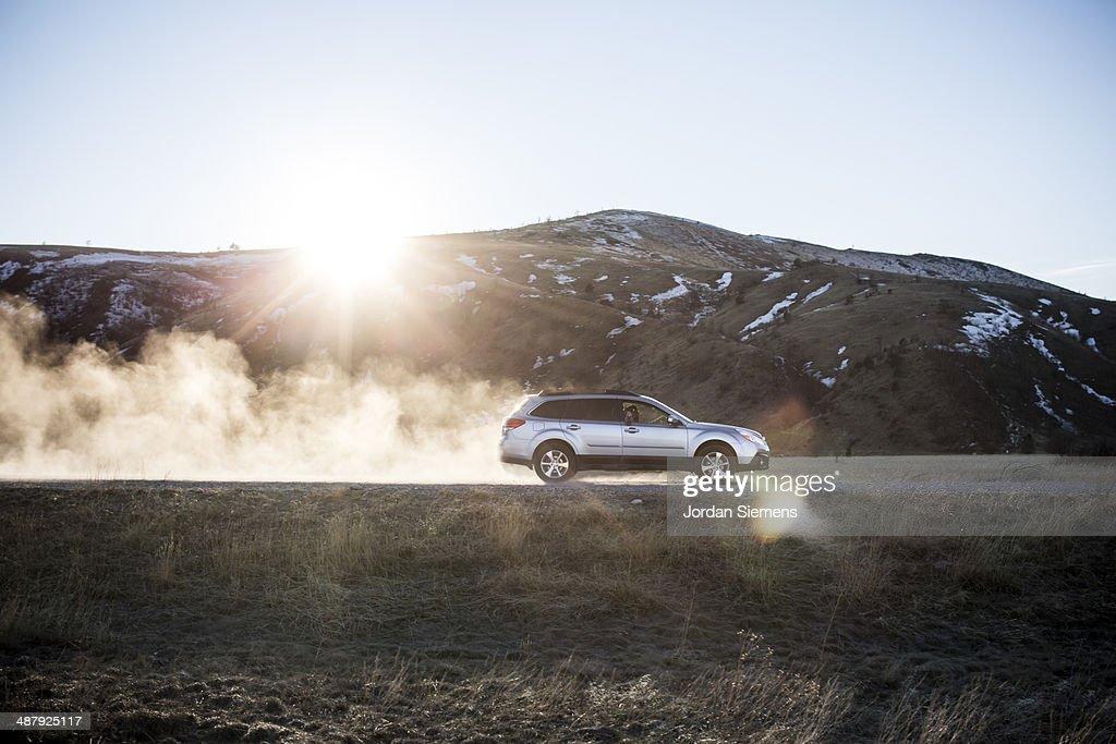 Car kicking up dust on dirt road. : Foto de stock
