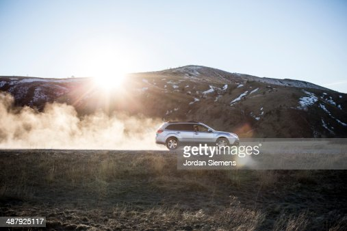 Car kicking up dust on dirt road. : Foto de stock