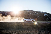 Car kicking up dust on dirt road.