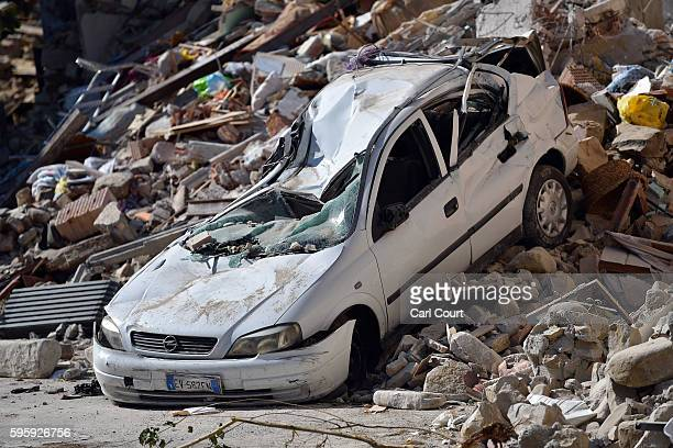 A car lies crushed by rubble after a building collapse during Wednesday's earthquake on August 26 2016 near Amatrice Italy Italy has declared a state...