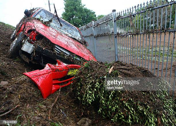 A car lies down an embankment after being washed off the road by a flash flood at Broughton Anglican College in Campbelltown on February 28 2007 in n...