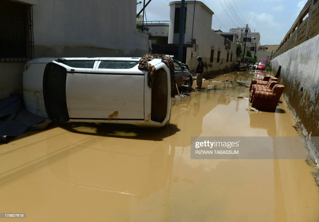 A car lies on its side in the aftermath of floods at a residential area of Karachi on August 5, 2013. Pakistani disaster relief officials issued fresh flood warnings after the death toll from heavy monsoon rains rose to 45 and waters paralysed parts of the largest city Karachi. Flash floods caused by monsoon downpours have inundated some main roads in the sprawling port city and swept away homes in the northwestern province of Khyber Pakhtunkhwa. AFP PHOTO / RIZWAN TABASSUM