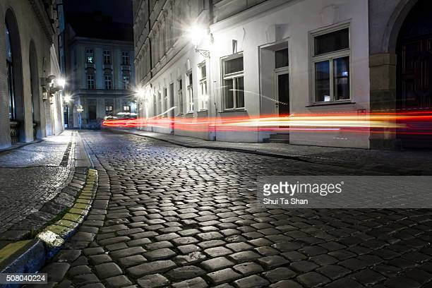 car light trail on cobblestone street in Prague