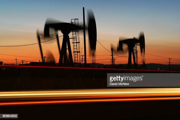 Car lights are seen streaking past an oil rig extracting petroleum as the price of crude oil rises to nearly $120 per barrel prompting oil companies...