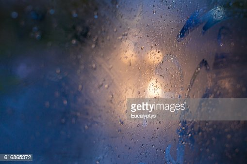 Car lights reflected in glass in rain : Stock Photo
