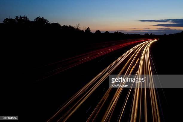 Car lights streaking into sunset