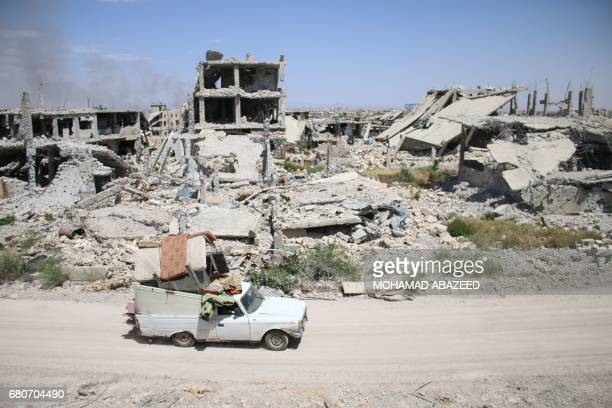 A car loaded with belongings of a displaced Syrian family drives past destroyed buildings in a rebelheld area of the southern city of Daraa on May 9...