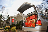 Car loaded with Christmas presents in driveway of home