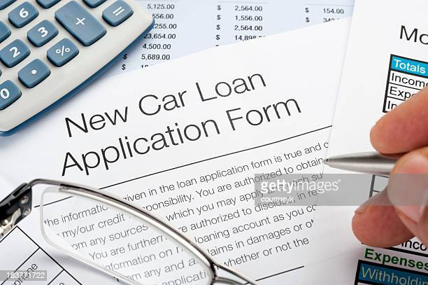 Car loan application Form with pen, calculator, writing hand
