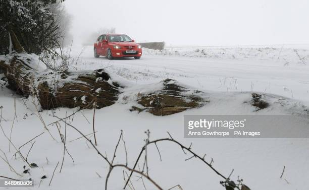 A car makes its way slowly down a snow covered road outside York as freezing weather hits the country