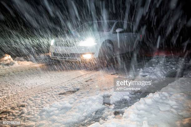 A car makes its way through heavy snowfall in Grasgehren near Oberstdorf southern Germany on November 5 2017 / AFP PHOTO / dpa / Bernd März / Germany...