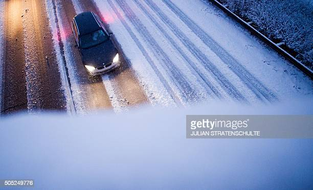 A car makes its way through the snowy A7 highway in Sehnde near Hanover central Germany on January 16 2016 / AFP / dpa / Julian Stratenschulte /...