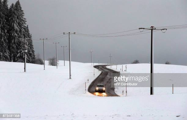A car makes its way through the snowy landscape in Goerisried southern Germany on November 13 2017 / AFP PHOTO / dpa / KarlJosef Hildenbrand /...