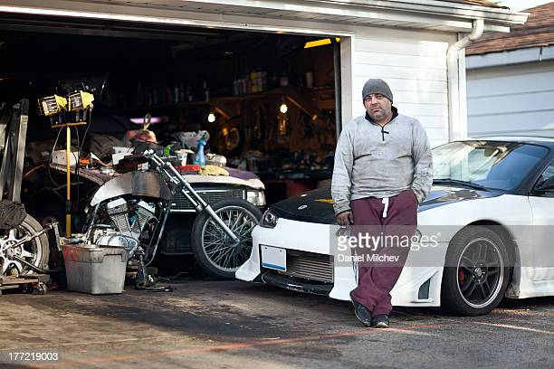 Car mechanic and his racing car, by his garage.