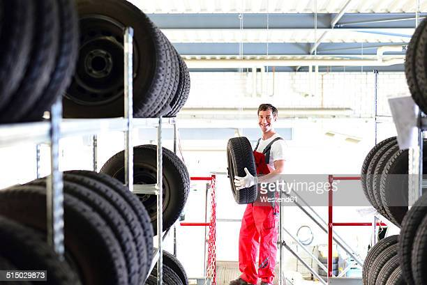 Car mechanic at shelf with tires